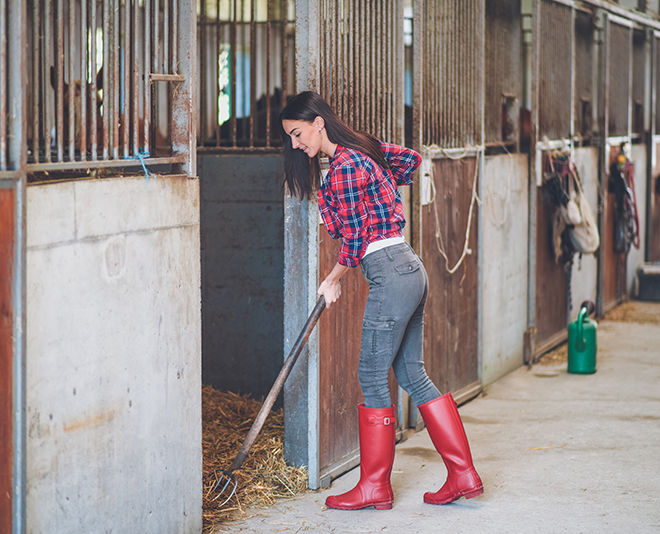A young woman cleans stable